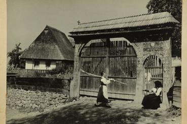 Fonó asszony és munkából hazatérő leány az utcán, a kapu előtt, Székelypálfalva