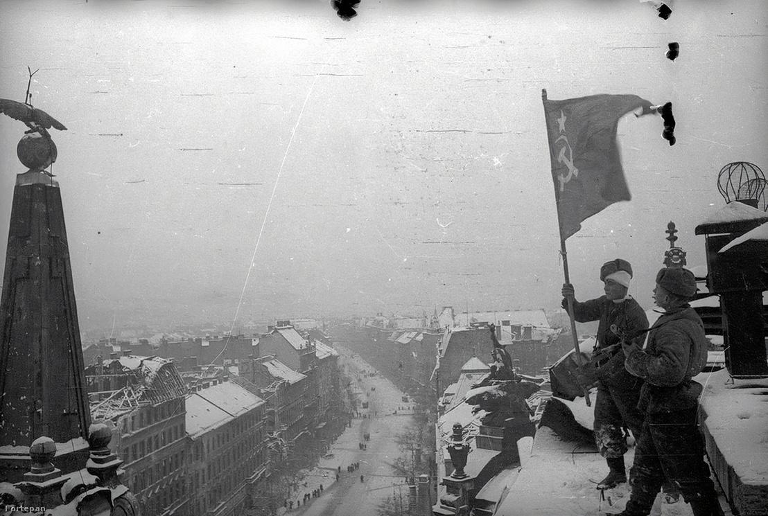A New York palota tetejére szovjet zászlót tűző katonák 1945-ben, az Erzsébet körúton.