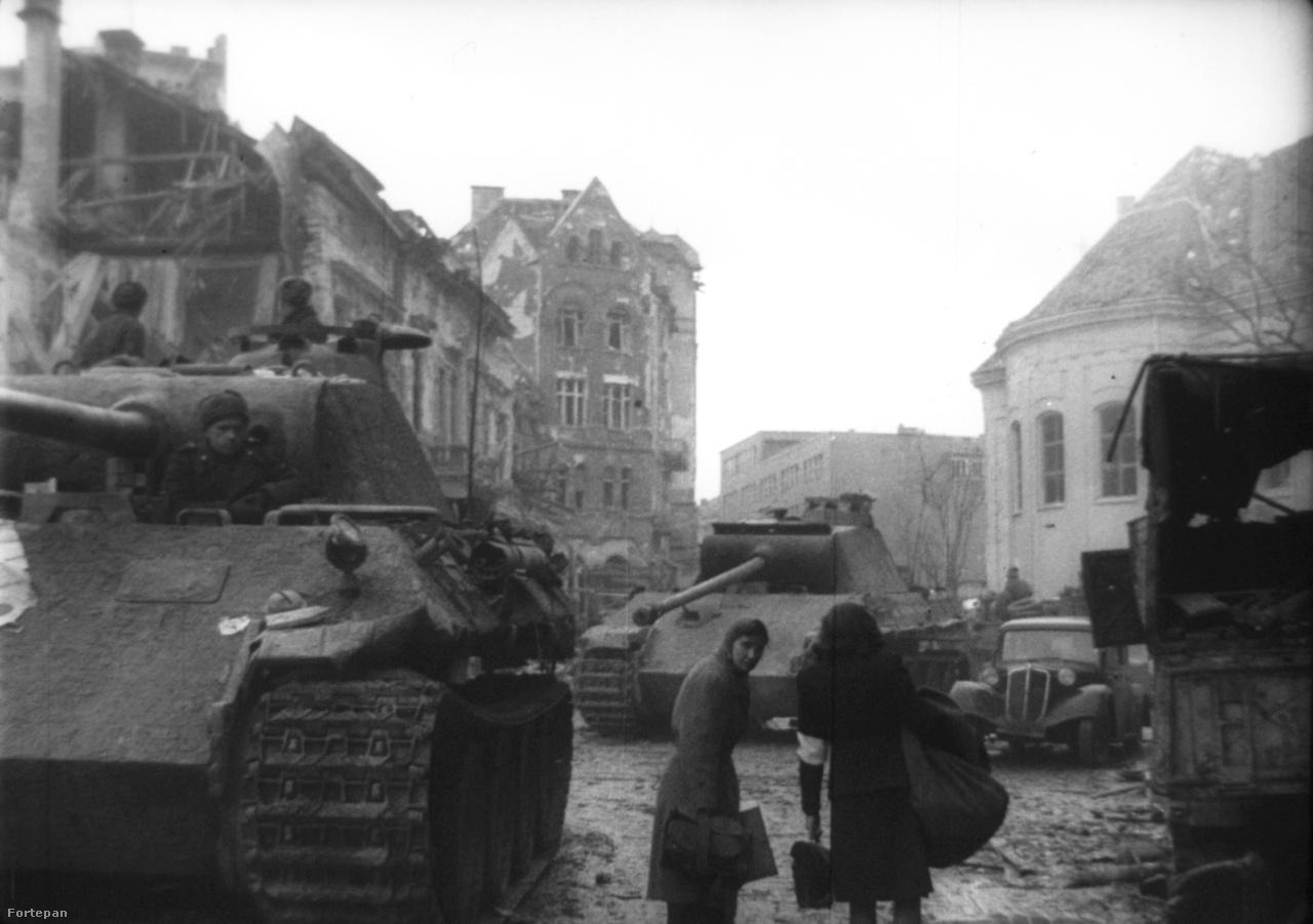 Ez a kép ugyanezt a Mészáros utcai helyszínt mutatja más                         szögből. Két nő csomagokkal igyekszik valahova, a szovjet katonák a német harckocsikat vizsgálják. A mai utcaképet ide kattintva nézheti meg.