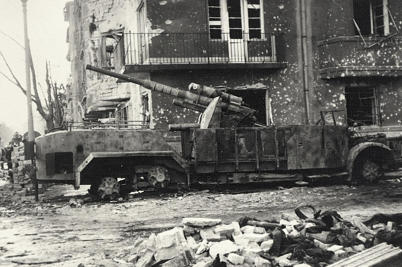 Ez a kép is a Batthyány tér déli sarkán álló német, Vomag önjáró légvédelmi löveget ábrázolja. A lövegcsőre felfestett fehér körök a megsemmisített ellenséges repülők számára utalnak. Ezen a második képen érdekes módon már nincsenek rajta a gumiabroncsok a kerekeken. A szovjet hadsereg és a budapesti lakosság is igyekezett mindent hasznosítani az utcán hagyott hadifelszerelésből. A mai utcaképet ide kattintva nézheti meg.
