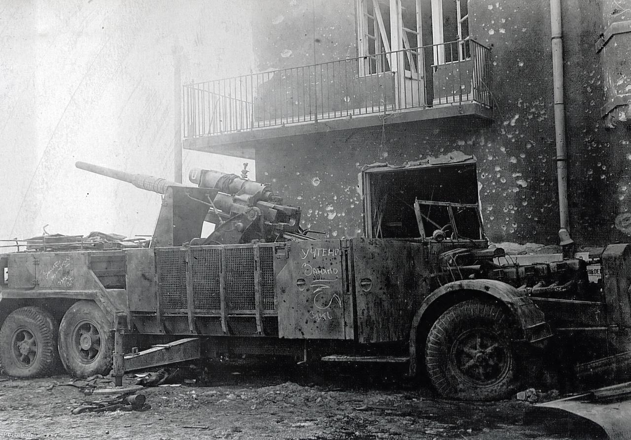 """A Batthyány tér déli sarkán elhagyott német Vomag típusú önjáró légvédelmi löveg. A 88 milliméteres légvédelmi ágyút a Vogtländische Maschinenfabrik által gyártott buszalvázakra szerelve félelmetes hatékonyságú gyorstüzelő légvédelmi egységeket állítottak fel 1941 után. A gép oldalán látható orosz felirat arra utal, hogy a löveget a Vörös Hadsereg leltárba vette (""""rögzítette"""") és lefoglalta. A mai utcaképet  ide kattintva nézheti meg."""