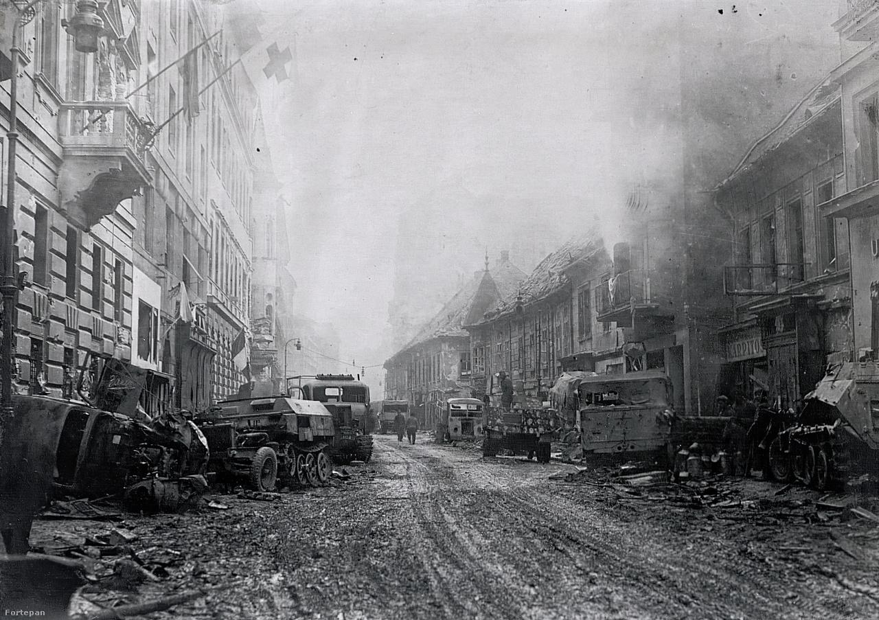 Két felvétel a Fő utcáról. Az elsőn jól látható, hogy éppen kiég az egyik lakás a jobb oldali harmadik épületben – az emeleti ablakon füst tör elő. Az utcán a német hadosztályok üzemképtelenné tett járművei láthatóak, baloldalon a 13. páncéloshadosztály Sd.Fkz. 250/9 könnyűfelderítő lövészpáncélosa. A mai utcaképet  ide kattintva nézheti meg.