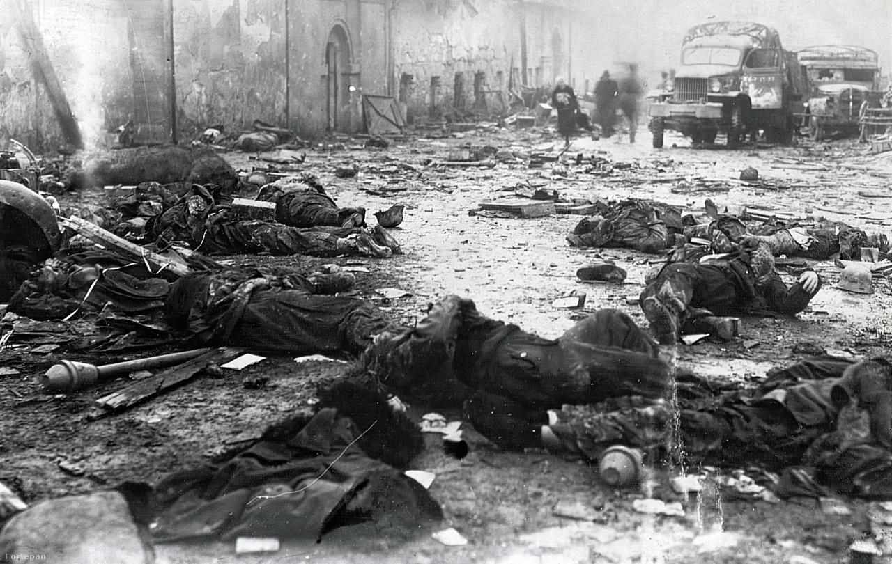A Varsányi Irén utca torkolata a Széll Kálmán térről nézve a kitörés halottaival. Az elmosódott alakok között egy nő botorkál egy cekkerrel. A halottakat a szovjet katonák már kifosztották, személyes tárgyaik az elszórt hadianyag közt hevernek. Bal oldalt az ostrom után elbontott régi Szent János kórház épülete látható, itt később a buszpályaudvart alakították ki. A mai utcaképet ide kattintva nézheti meg.