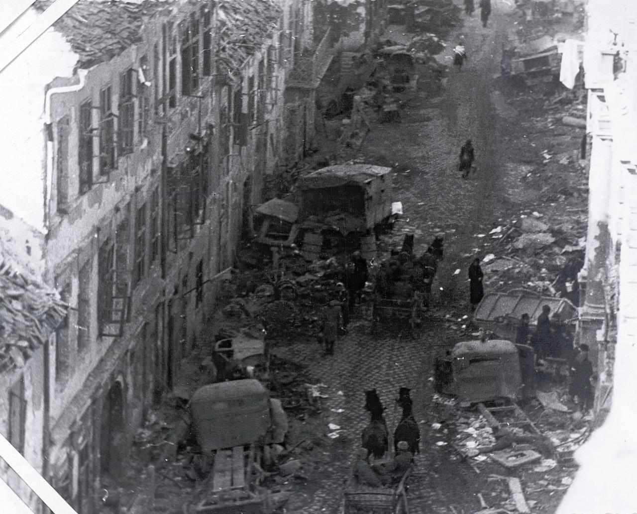 """A Döbrentei utca északi irányba, a Döbrentei 16., 18. vagy 20. számú házból fotózva. A felvétel közvetlenül az ostrom után, 1945. február 13-15 között készülhetett. Ez az utcán heverő lomok mennyiségéből is valószínűsíthető. A kép azonosítása nem egyszerű, mert később szinte mindent lebontottak, ami a felvételen látható. A bal oldalon a Döbrentei utca 15. szám erkélye, és kivehető az épületek előtt húzódó, az utca 19. század végi feltöltésekor keletkezett """"süllyesztett"""" járda, illetve annak korlátja (a kép bal alsó sarka közelében), valamint a kép felső részében az 15. szám erkélye mellett-mögött a feljáró lépcső néhány foka. Minden más ma már nem látható. A mai utcaképet ide kattintva nézheti meg."""