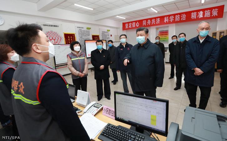 Hszi Csin-ping kínai elnök (k) az új koronavírus-járvány terjedésének megakadályozására tett intézkedésekről tájékozódik Peking egyik kerületében 2020. február 10-én.