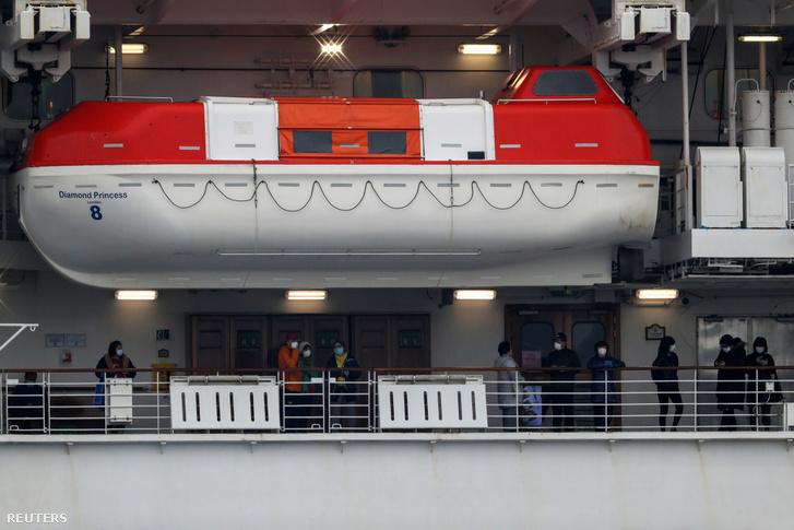 Arcmaszkban lévő utasok a Diamond Princess karanténba zárt hajó fedélzetén 2020. február 16-án a Daikoku hajókikötőben, Jokohamában