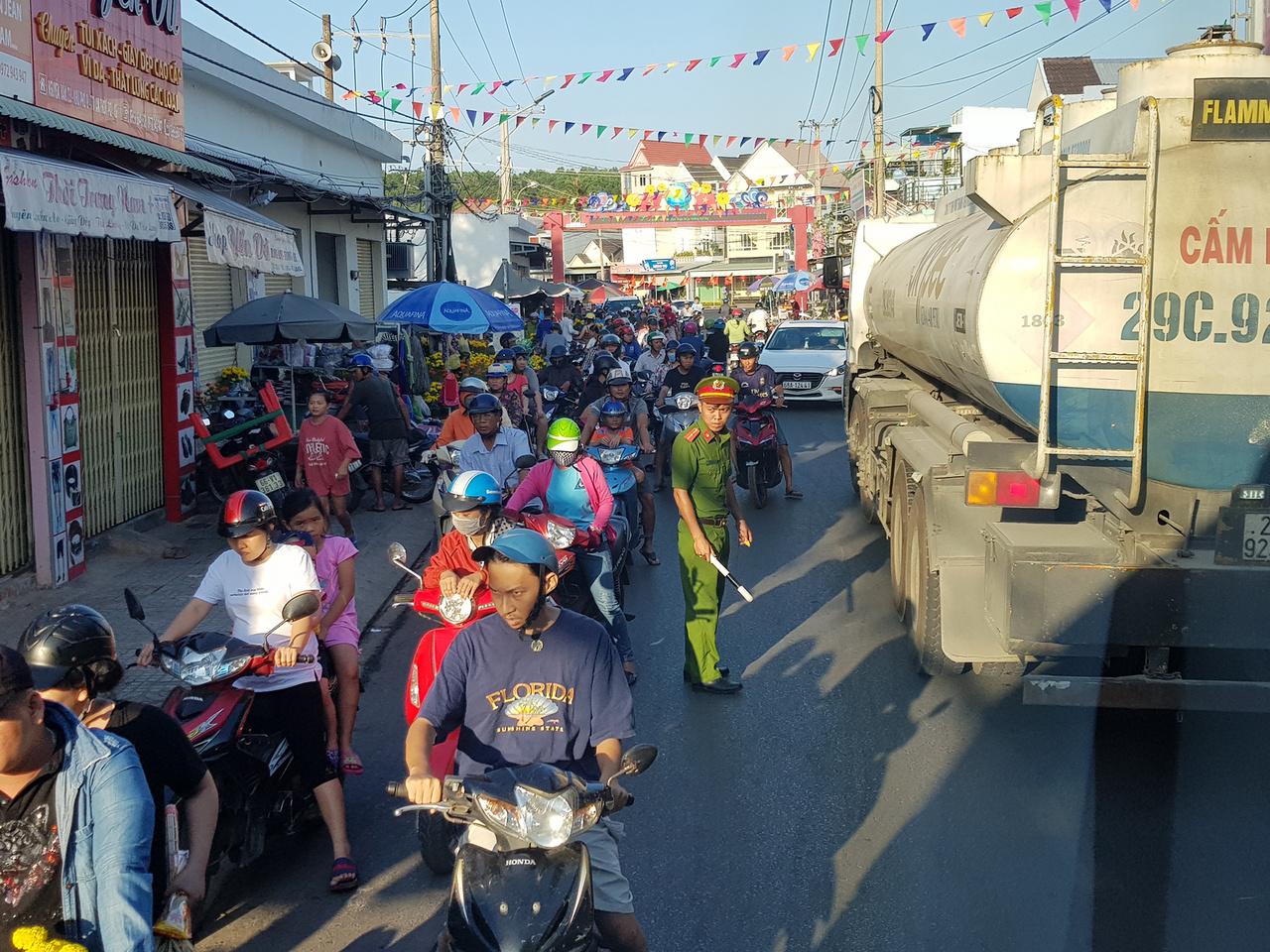 Forgalmi dugó a Phu Quoc szigetén található An Thoi városkában. A kínai holdújév miatti ünnepségek alatt sok utcát lezártak, így a nehézgépjárművek is szűk utcákba kényszerültek. A képen látható tartálykocsi úgy fért el, hogy a tetejére mászott egy jóképességű, aki a villanyvezetékeket és távközlési kábeleket bottal tartotta araszolás közben. Közben mindenki türelmetlenül nyomta a dudát, mintha nem lenne holnap. A káoszt a körzeti meghízott megjelenése sem csillapította. Volt több olyan idióta, aki majdnem a teherautó kerekei alá került, de ő akkor is megy tovább, ha van hozzá hely, ha nincs