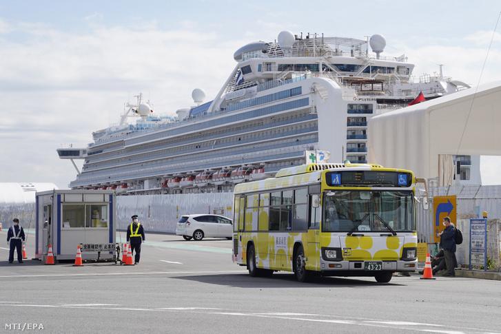 A jokohamai kikötőben karantén alá vont Diamond Princess amerikai óceánjáró utasai a 14 napos karantént követően busszal távoznak 2020. február 19-én.
