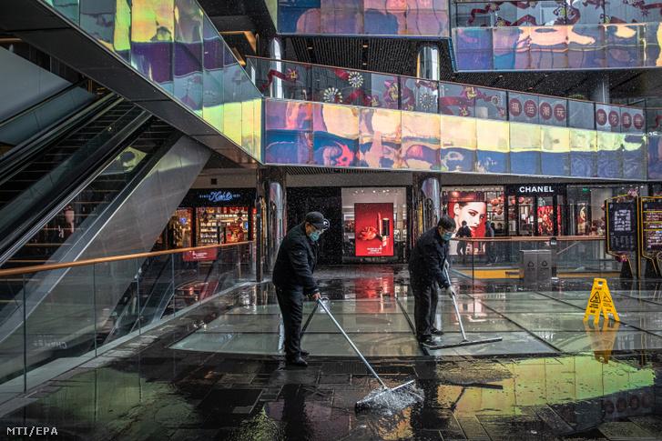 Védőmaszkos takarítók a csaknem néptelen Szanlitun pekingi bevásárló- és szórakozónegyedben ahol sok üzlet továbbra is zárva tart az új koronavírus miatt 2020. február 14-én.