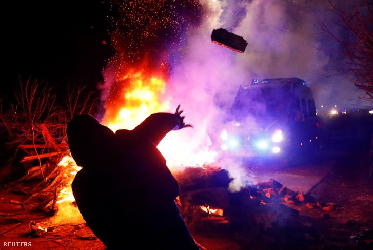 Tüntető dobja meg a rendőrkocsit a koronavírus miatt hazaszállított betegek miatti tüntetésen Novi Szanzsariban 2020. február 20-án