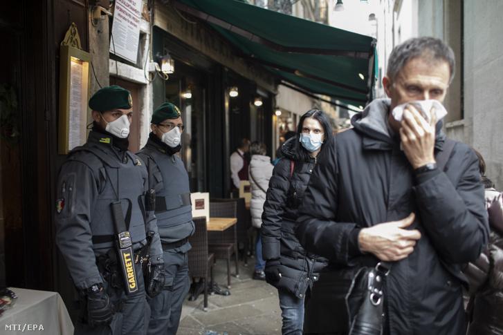 A koronavírus elleni védekezésül szájmaszkot viselő rendőrök és turisták a velencei karneválon a Szent Márk tér közelében 2020. február 23-án