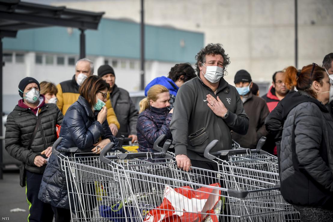 Sorban állnak az emberek egy Lidl áruház előtt az észak-olaszországi Casalpusterlengo településen 2020. február 23-án