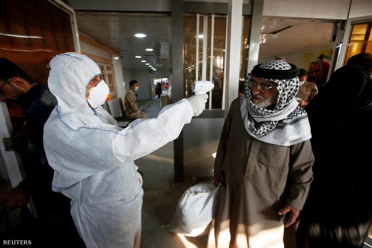 Egészségügyi dolgozó ellenőrzi az utazók hőmérsékletét az iráni–iraki határon Shalamcha határátkelőnél 2020. február 20-án