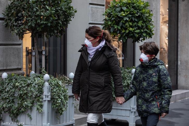 Nő és a fia egészségügyi maszkban sétál Milánóban.