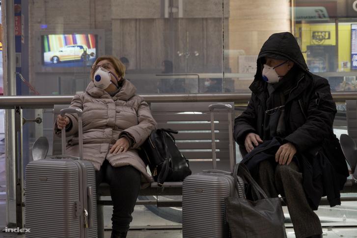A milánói főpályaudvaron maszkban várakozó utasok