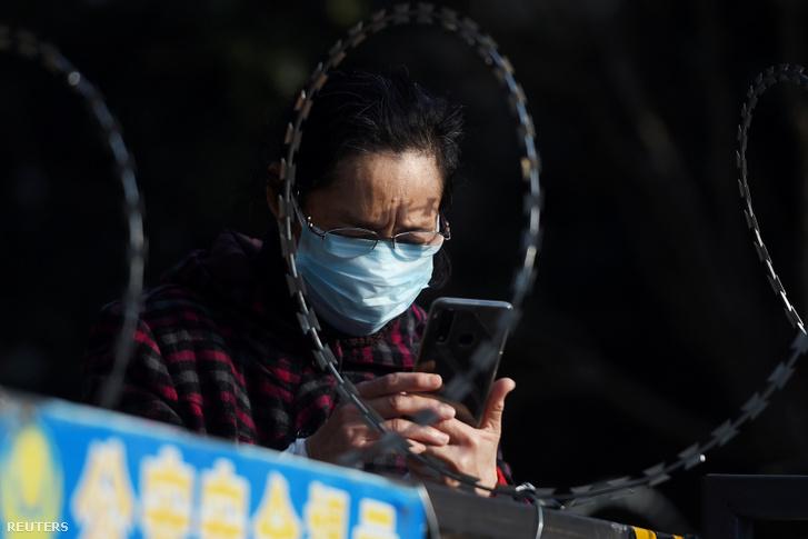 Egy vuhani nő mobilozik szögesdróttal körbevett lakótelepi otthona előtt, 2020. február 22-én