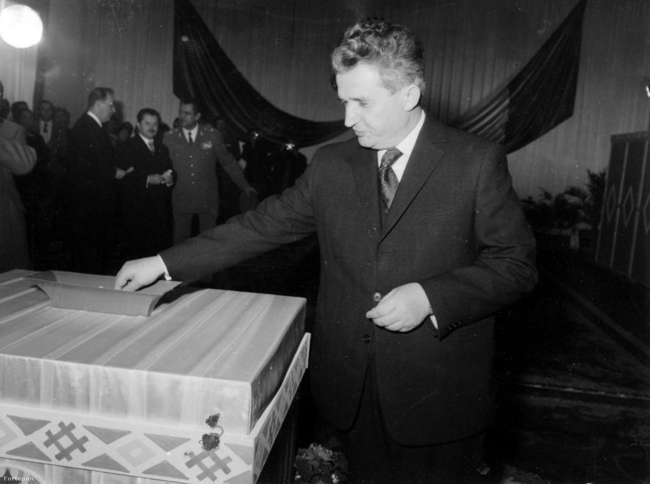 """Nicolae Ceaușescut 1974-ben választották Románia első elnökévé. A kárpátok géniusza itt alighanem sajét magára szavaz. Ekkor már kilenc éve töltötte be a Román Kommunista Párt főtitkári posztját, az országban mind jobban elhatalmasodott a személyi kultusz. Az Új Élet Ceaușescu elnökké választását """"történelmünk nagy pillanatának"""" nevezte, és a kor divatjának megfelelően nagy összeállításban emlékezett meg a pártvezér életéről. A kép hátterében Manea Manescu román miniszterelnök, jobbra mellette Fazekas János erdélyi magyar politikus, a Román Kommunista Párt Politikai Végrehajtó Bizottságának tagja. Ceaușescut 1989-ben kivégezték. A Ceaușescunál két évvel idősebb Manescu felesége Ceaușescu lánya, Maria volt. Manescu 2009-ben halt meg Bukarestben. Az újságíróként és történészként is ismert Fazekas János Sütő András szerint magas állami és párttisztségeiben (vagy azok ellenére) sokat tett az erdélyi magyarságért. 2004-ben Budapesten halt meg, az MTA megbízásából kutatott a magyar fővárosban."""