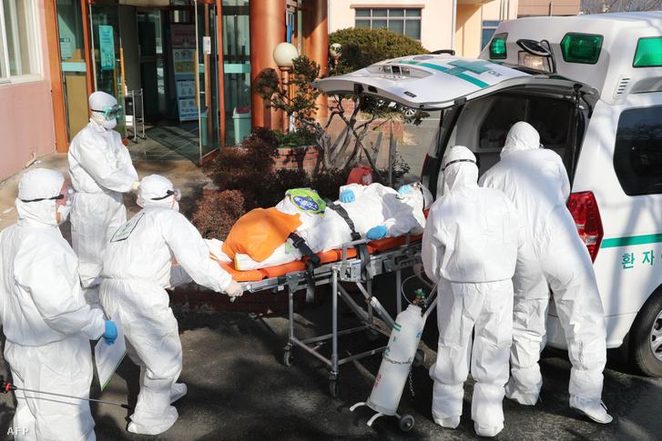 Egészségügyi alkalmazottak koronavírusos beteget szállítanak egy másik kórházba