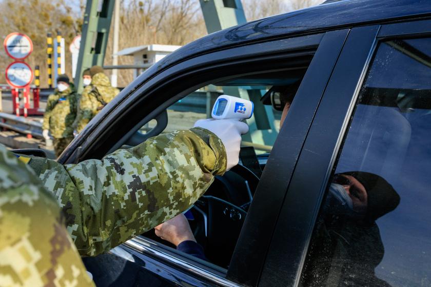 Ukrán határőr méri egy hazafelé érkező gépkocsivezető testhőmérsékletét az ukrán-magyar határon.