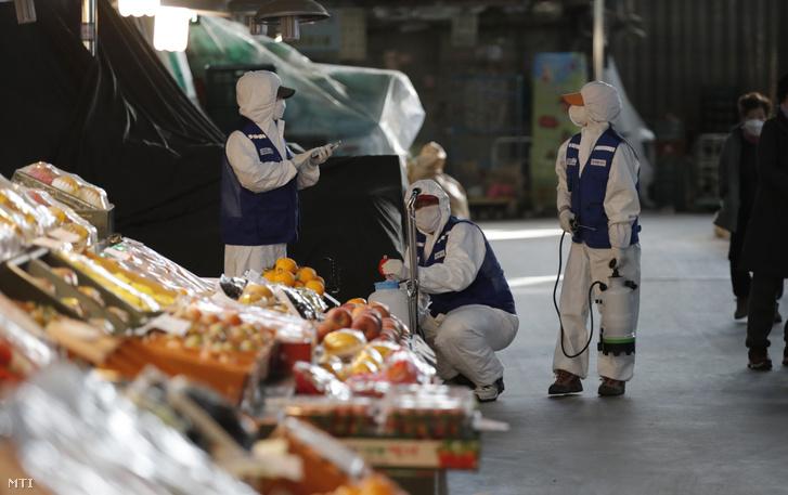Védőruhát viselő egészségügyi alkalmazottak fertőtlenítenek a tüdőgyulladást okozó új koronavírus-járvány elleni védekezésül egy szöuli piacon 2020. február 27-én.