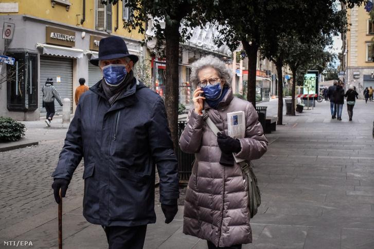 Arcmaszkot viselő járókelők Milánóban 2020. február 26-án.