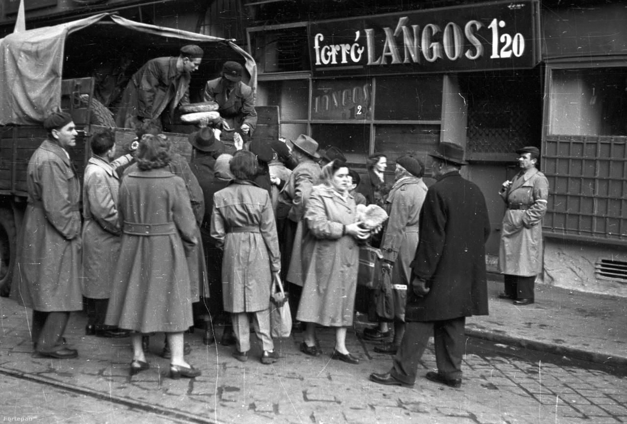 Forradalom esetén különösen fontos kérdéssé válik a kenyérellátás. 1956 október végén a vidéki városokból sok segítség érkezett Budapestre, a kenyérszállító teherautók is többször fordultak egy nap. A fővárosi pékek napokig dolgoztak folyamatosan, hogy a felfokozott hangulatban is legyen elég kenyér, amit aztán gépkarabéllyal felfegyverzett nemzetőrök felügyelete mellett osztottak ki, mint ezen a Visegrádi utcában készült képen is láthatjuk.