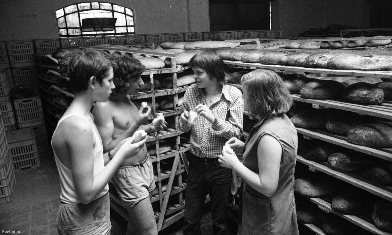 """Diákmunkásokkal beszélget egy diáklap szerkesztője a Petneházy utcai kenyérgyár raktárában ezen az 1974-es fotón. A gyárat még 1911-ben építették """"a kenyérínség enyhítésére és a kenyérárak szabályozása céljából"""". A munkatermek végig porcelán- és üvegburkolattal voltak ellátva, mint a sütőtermek is, ahol az átadás után 18 óriási gőzkemencében óránként 2000 kiló kenyeret tudtak sütni. Az államosított gyárban készülő kenyér minősége a hetvenes évek végére jelentősen romlott, a termékeket a vevők nem keresték, ezért a gyár bezárása mellett döntöttek."""