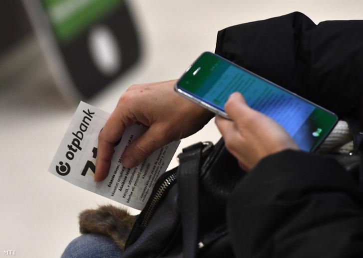 Képünk illusztráció! Okostelefonját használja egy ügyfél sorszámával kezében