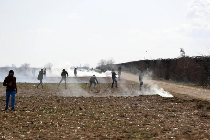 Menekültek követeket dobálnak a görög rendőrök felé a pazarkulei szárazföldi határátkelőnél a törökországi Eridne közelében 2020. március 2-án.