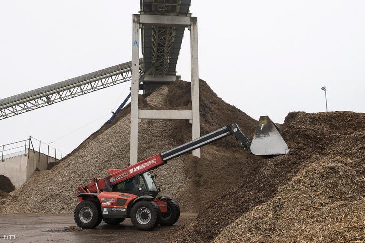 Faaprítékot markol egy munkagép a Dél-nyírségi Bioenergia Művek Zrt. Szakolyi Biomassza Erőművében