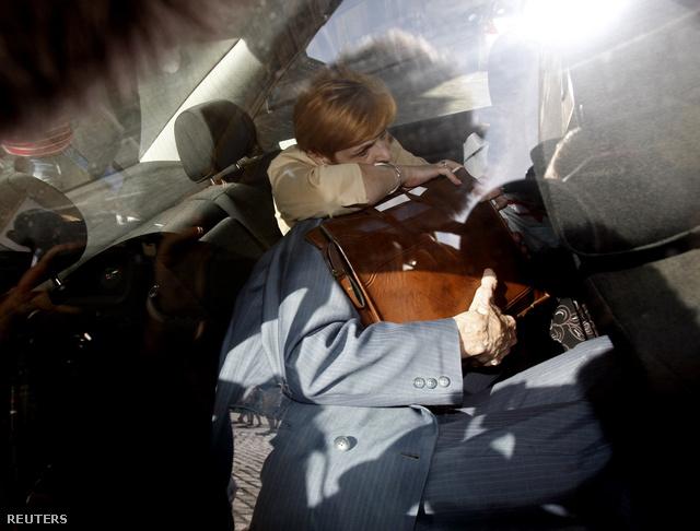 Az ügyészségről távozó Csatáryt ápolója védi a fotósoktól