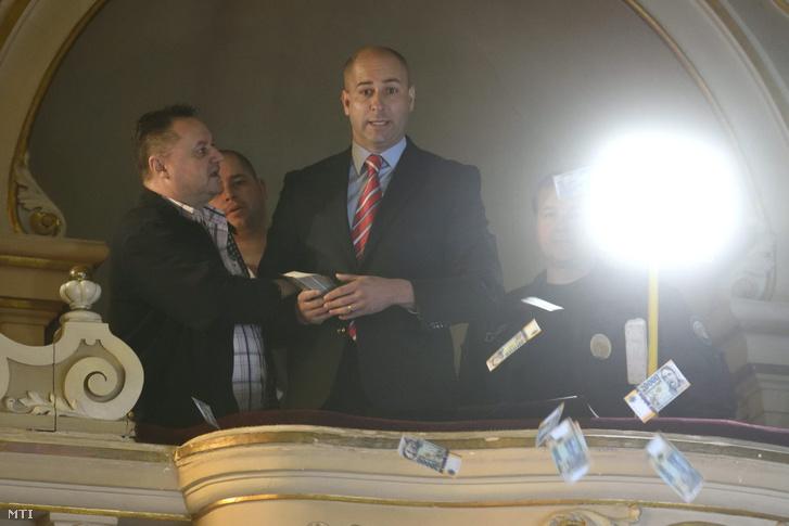 Szabó Bálint a Szeviép cégcsoport alvállalkozóinak egy részét képviselő Likvid Kontroll Kft. ügyvezetője (k) játékpénzeket szór le a szegedi városháza dísztermének karzatáról a közgyűlés ülése alatt 2017. március 31-én. A Szeviép-ügy miatt alakult ki vita az ülésen.