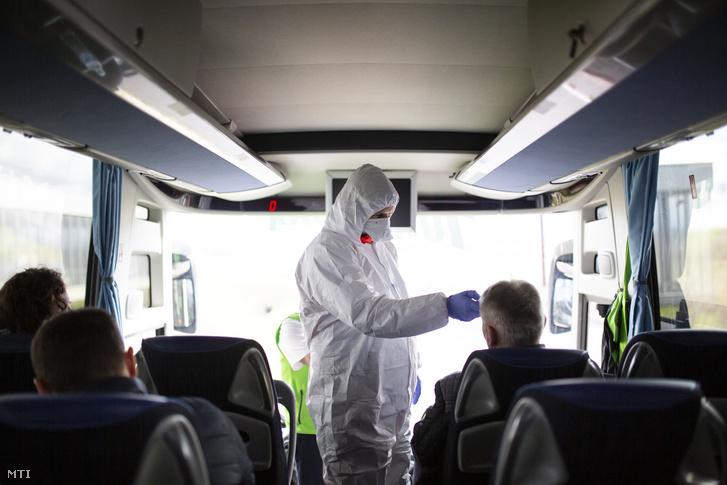 Mentőápoló ellenőrzi egy érkező busz utasait a koronavírus-járvány miatt a letenyei határállomáson 2020. február 5-én