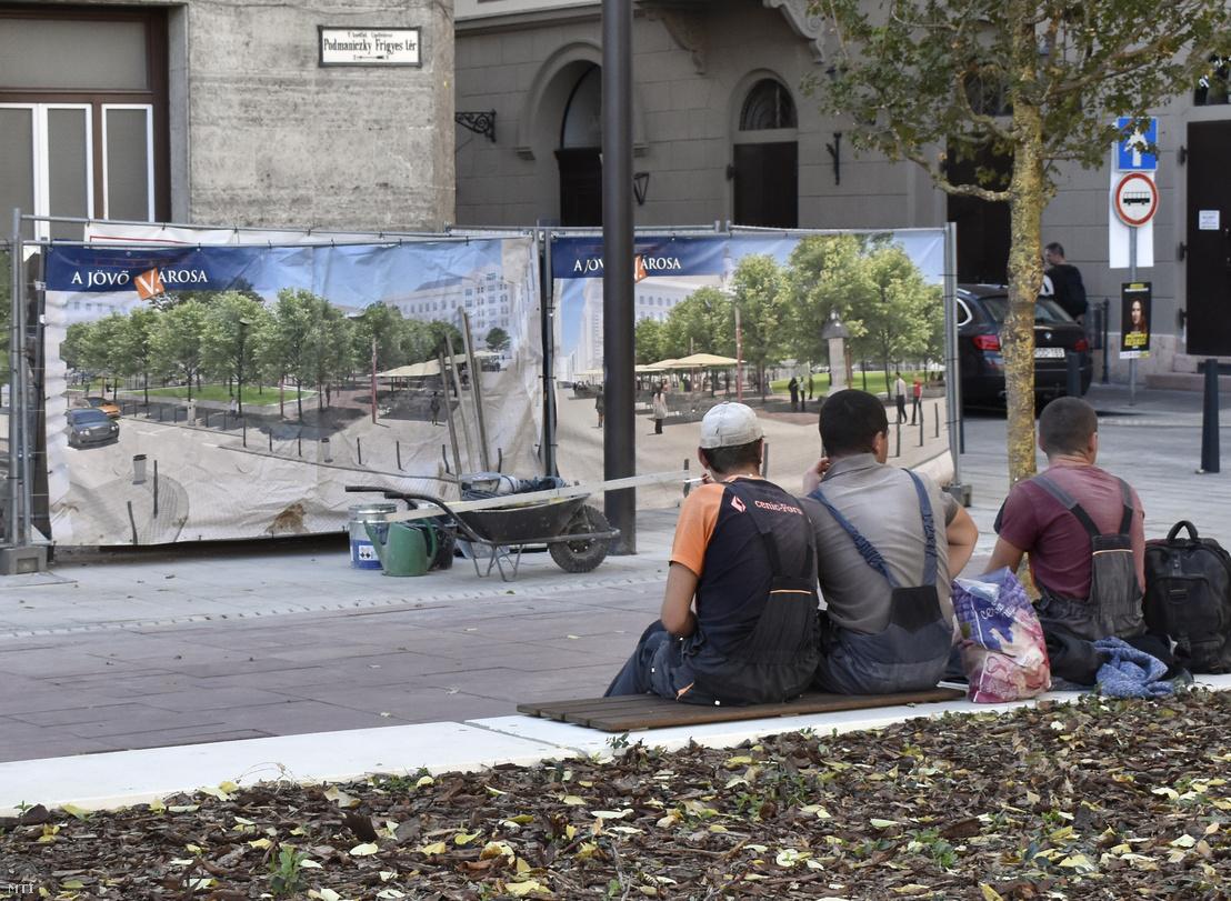 Munkások pihennek egy városfelújítást hirdető mobilkerítés előtt