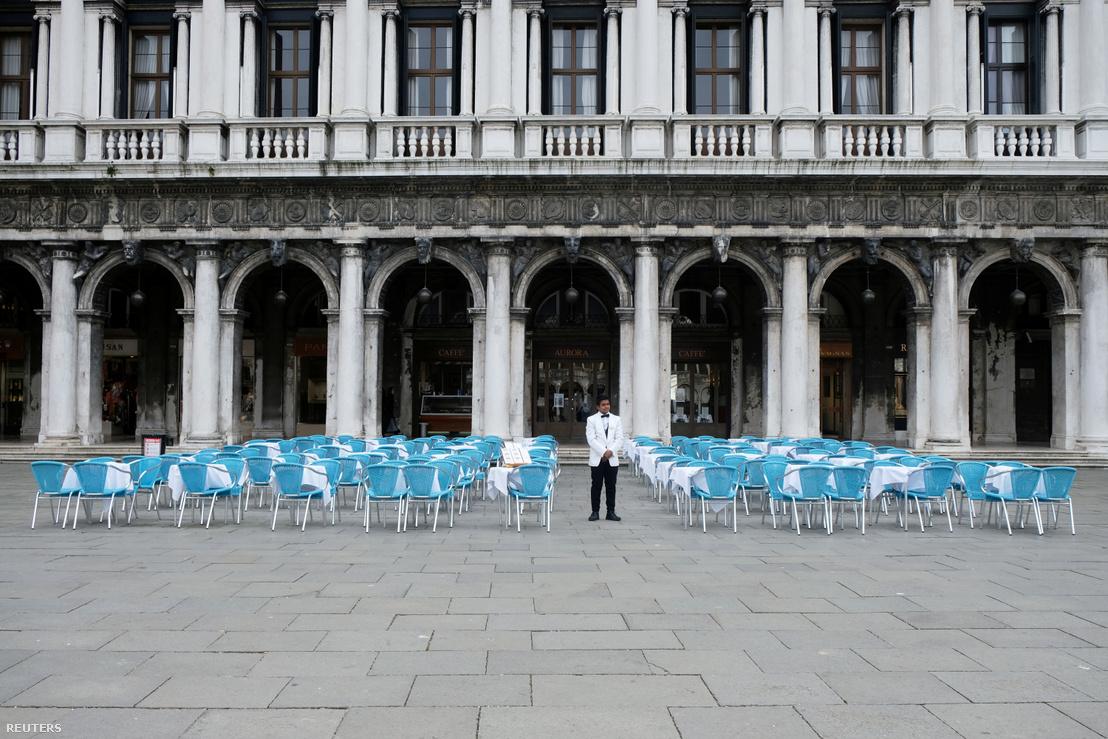 Pincér áll az üres asztaloknál a velencei Szent Márk téren 2020. március 5-én