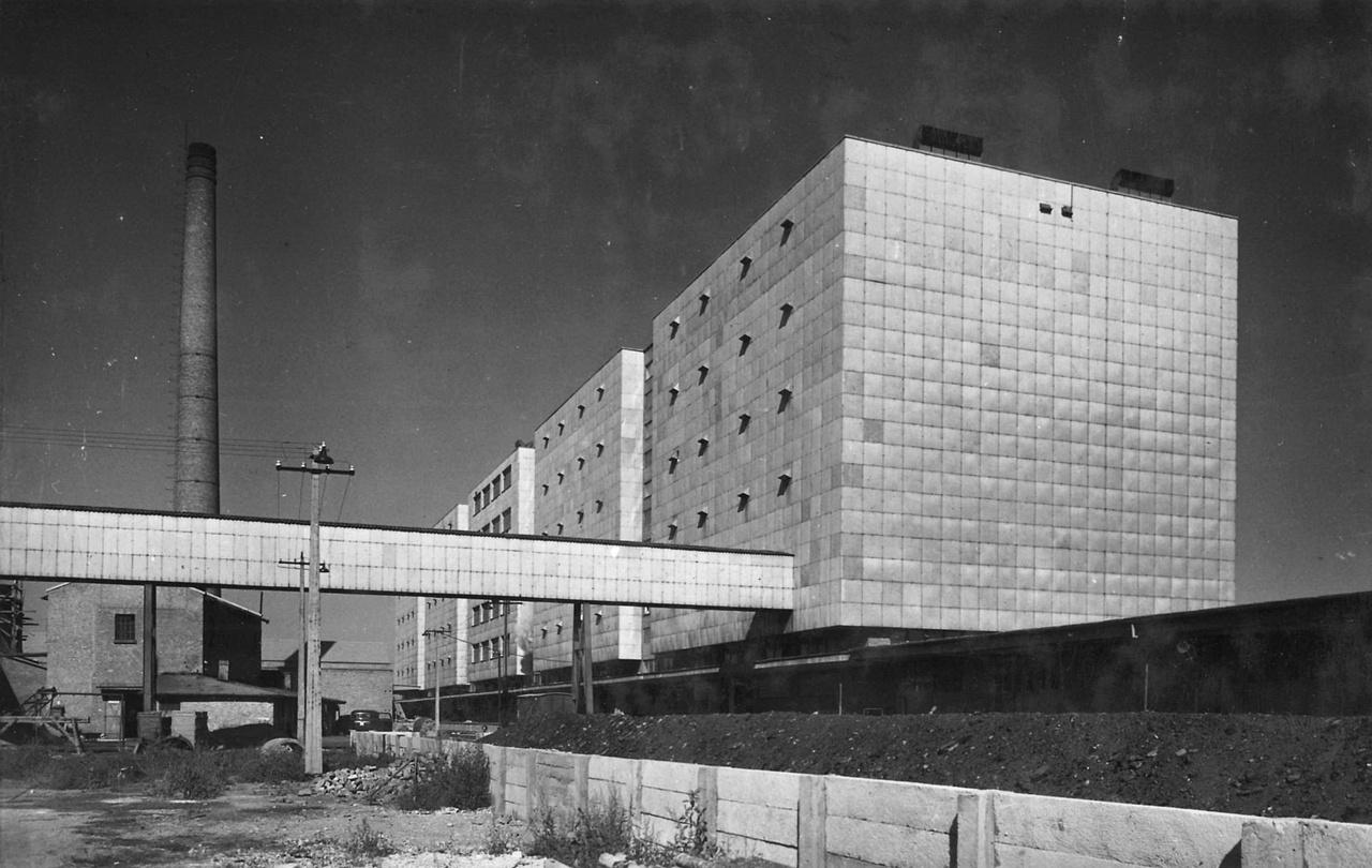 Rimanóczy Gyula, kinek legismertebb alkotása a Pasaréti téri templom, 1949-ben tervezte ezt a dohányfermentáló üzemet, Nyíregyházán. A második világháború után, erőltetve megindult iparosítás renegeteg új épületet igényelt. Olyan házakat, amilyenekre korábban nem volt szükség. Ha valaki jó lakóházat, hivatalt vagy előadótermet akart tervezni, akkor több száz vagy akár több ezer év tapasztalatát használhatta fel. A szocializmus ipari boomjában szinte minden épületnél ki kellett találni valami új technológiát. Talán ennek is köszönhető, hogy az ipari építészetből soha nem szorult ki teljesen a modern.