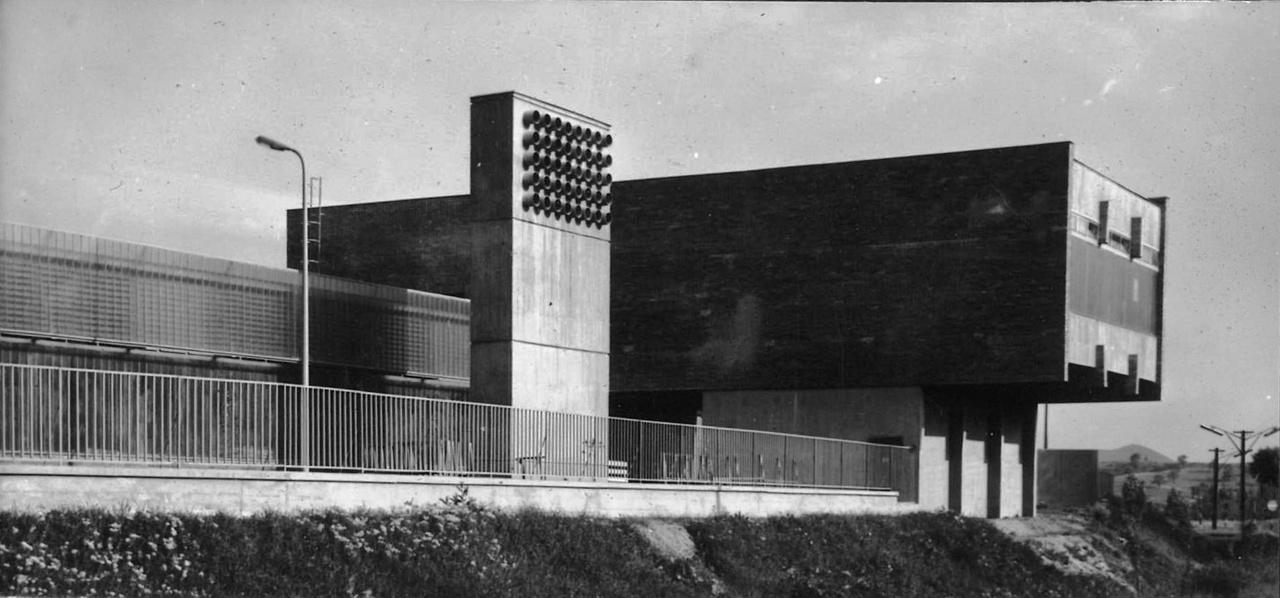 Ez a futurisztikusnak tűnő létesítmény pedig már a Salgótarjáni Síküveggyár edzőcsarnoka (ahol természetesen nem a dolgozók izmait, hanem az üveget edzették). Az épület kettős profilüveg falának klimatikus oka van, mint ahogy a betonhasáb sem csak dísznek áll ott: az a hűtőlégtorony. Igaz, szoborként is megállná a helyét. Izgalmas kompozíciót alkot a csarnokra merőleges transzformátorház tömegével. Elekes Keve István, Szontágh László, Márton Botond, 1964-1968.