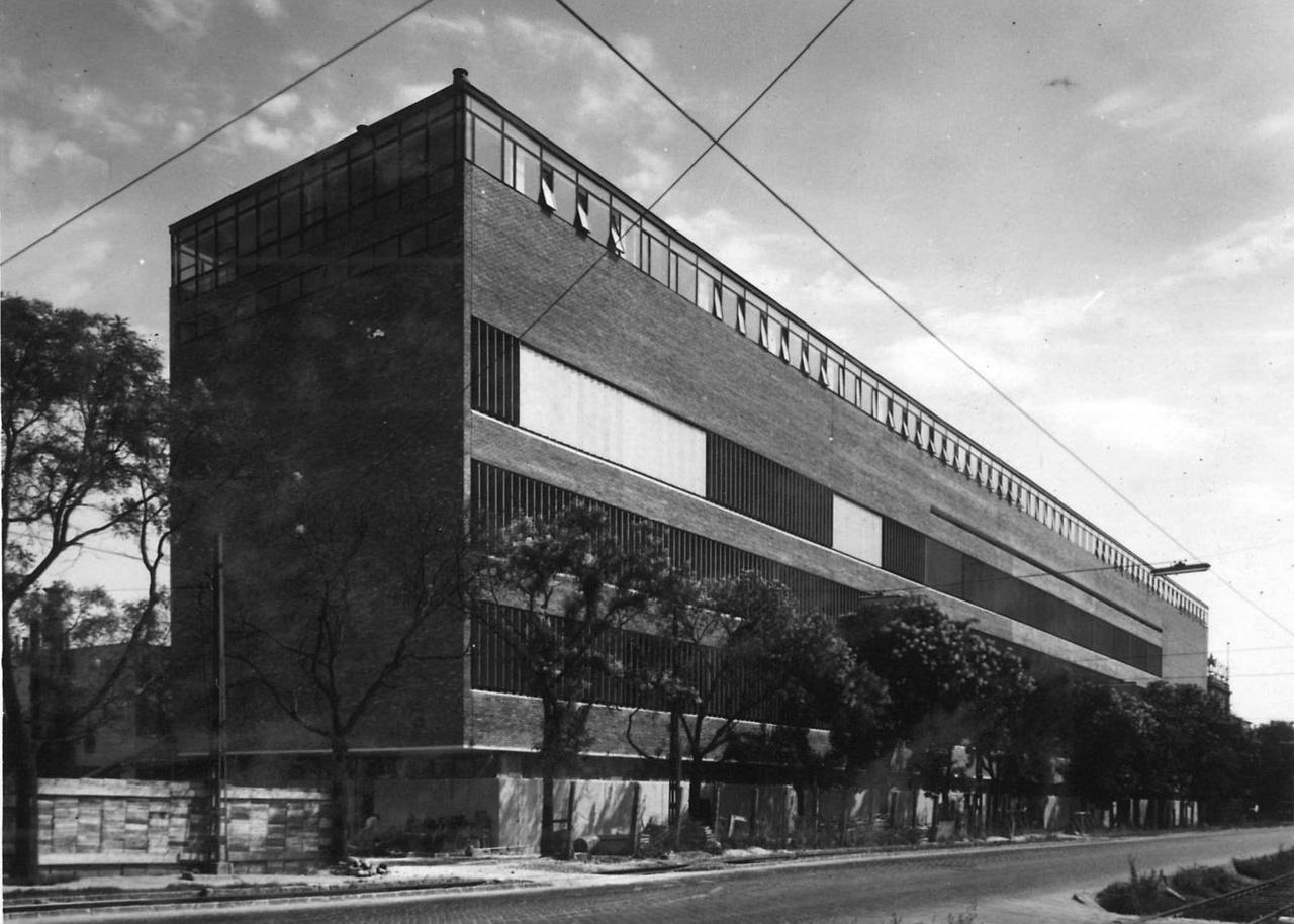 A Belloiannisz Hiradástechnikai Gyár 1964-re elkészült üzemi főépülete nem csak azért érdekes Kelenföldön, mert már olyan szellemben épült, hogy a belső tereivel alkalmazkodni tudjon a folyamatosan változó gyártásmenethez. Hanem azért is, mert olyan homlokzattal épült, mely tekintettel volt a városi környezetre. Tervezője Szendrői Jenő, és Pozsgai Lajos mellett Arnóth Lajos volt, aki halála évében mesélt építészeti hitvállásáról a Ház+ Mesterek videósorozatban.
