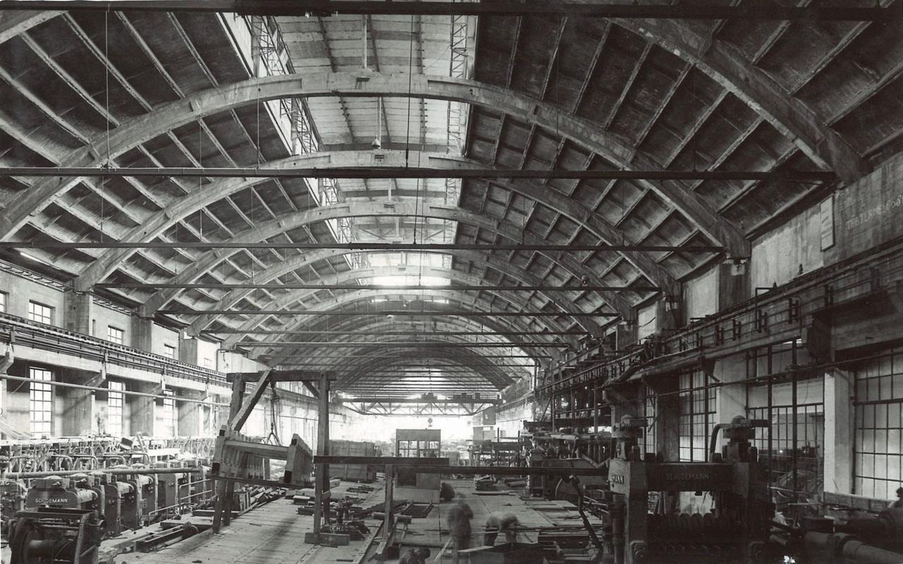 Mikor elkezdték építeni a diósgyőri kohászati műveket, még MÁVAG-nak hívták, de menet közben Leninre nevezték át. Az úgy nevezett középhengerműnél olyan technológiára volt szükség, amellyel hatalmas  összefüggő teret lehet áthidalni, alátámasztások nélkül. Az íves főtartókkal kialaktott belső tér közel harminc méter széles, és 335 méter hosszú lett. (Resatkó Endre, Nagy József 1950-1955.)