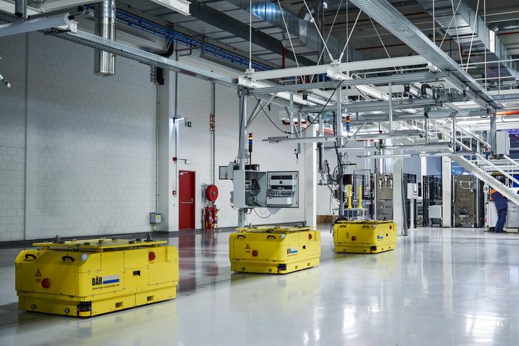 Ilyen cuki robotok mozgatják a szerelősoron az akkumulátor-csomagokat, melyeket aztán zárt egységként csavaroznak az elektromos Volvók hasára
