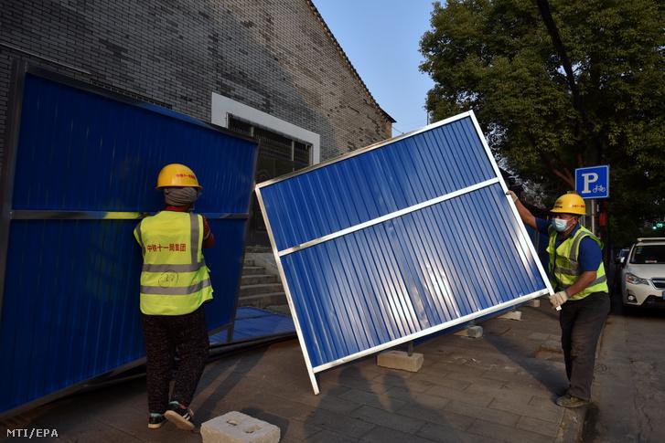 Kerítést építenek munkások egy vuhani lakónegyed köré 2020. február 23-án