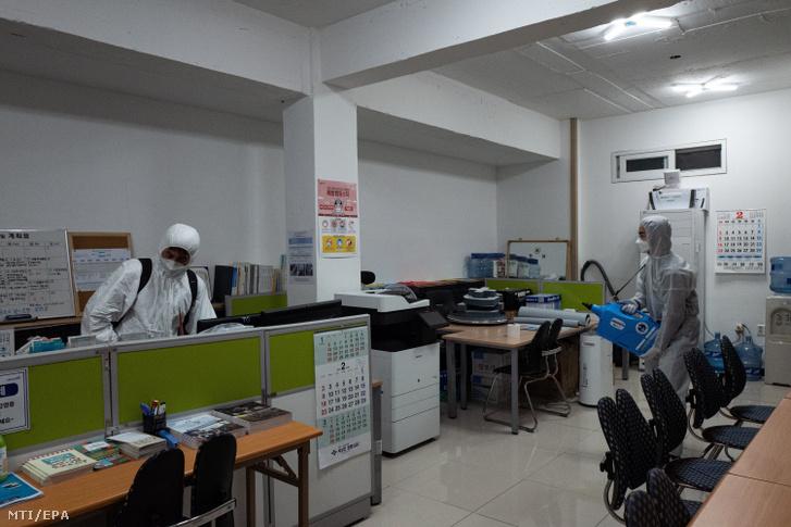 Egészségügyi alkalmazottak fertőtlenítenek a koronavírus elleni védekezésül egy irodaépületben a szöuli Szemaul piacon 2020. február 26-án.