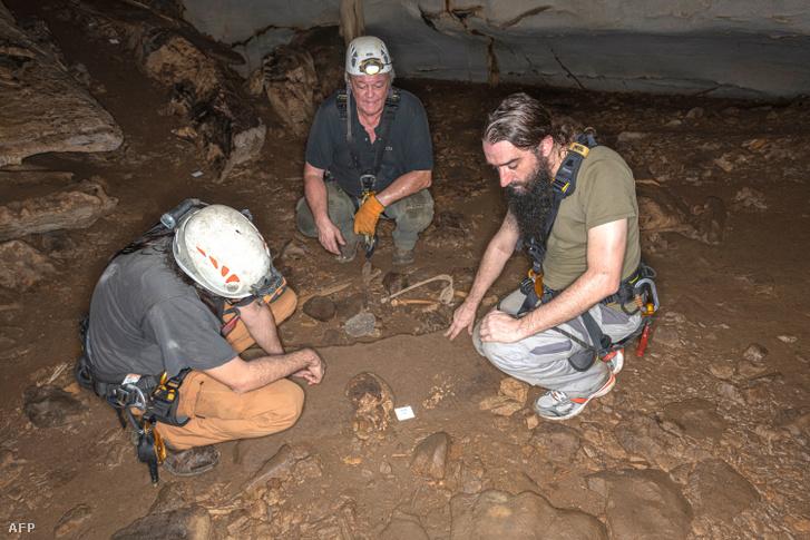 Richard Oslisly geoarcheológus (középen), illetve Sebastien Villotte (balra) és Sacha Kacki antropobiológusok vizsgálják egy emberi koponya maradványait a gaboni Iroungou barlangban 2020. március 3-án.