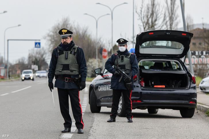 Olasz Carabinieri fegyveres rendőrök ellenőrzik a forgalmat a karanténba helyezett Modena és Bolonga tartomány határán 2020. március 9-én