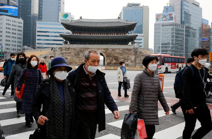 Arcmaszkban sétáló emberek Szöulban 2020. március 9-én