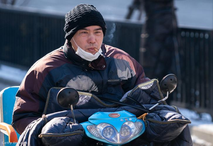 Halmozott veszélyek, motorozás sisak nélkül, arcmaszkban dohányozva Kínában 2020. február 9-én