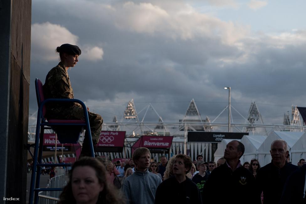Több ezer katonát vezényeltek az olimpiára, miután kiderült, hogy a felfogadott magán biztonsági cég nem bírja ellátni a dolgát. A fiatal katédlányt felültették arra az emelvényre, ahonnan a tömeget kéne irányítani. Hangosan, vidáman. Hát a kiképzésben sajnos erről egy szó sem volt, így csak hallgat és mosolyog. De ez is elég.