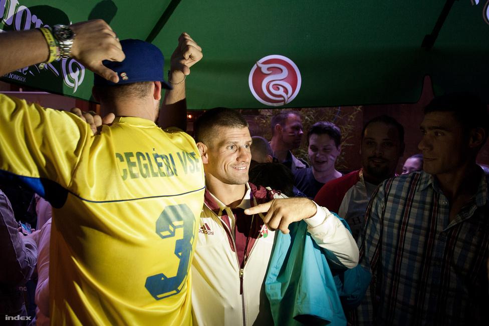 A londoni olimpia magyar szurkolói kocsmája Archway-ben, amit nem csak a Soproni molinóról, meg a Fornetti pogácsa adalékanyagokkal felturbózott illatáról lehet megismerni, de ha valakinek ennyiről még nem ugrana be a dolog, hát minden vendég piros-fehér-zöld zászlót is pingált az arcára. Vagy legalábbis hagyta, hogy mások ezt tegyék vele.                         A magyar férfi kézilabda válogatott smúzol éppen a szalonspicces tömeggel, a hangulat pattanásig feszült: ha valaki azt mondja, hogy ria-ria, hát két tucat ember feleli rögtön szinte eksztázisban, hogy Hungária. Figyelembe véve, hogy 3,5 font, azaz 1300 forint egy korsó Soproni, meglepő azért ez a lelkesedés.