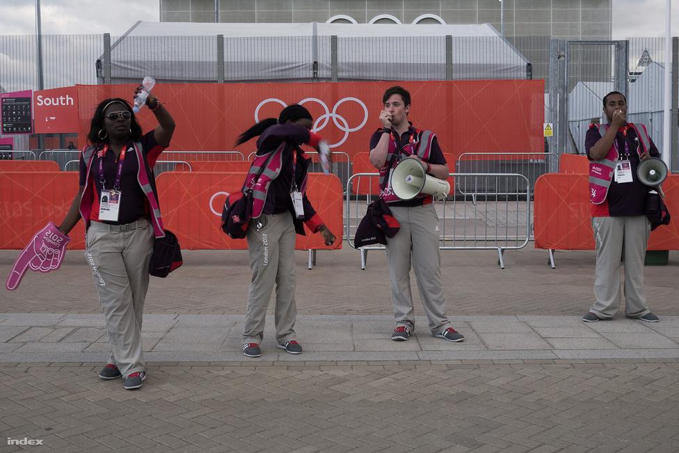 A londoni olimpia egy kicsit túl van biztosítva, a legtöbb helyen, ahova azt kéne kiírni, hogy Kijárat, hát ott van egy Exit tábla egy rúdon, amit egy fickó szorongat, és mosolyogva még hozzáteszi, hogy erre van a kijárat.                          Na, az önkéntesek közül azok jártak a legjobban, akik kaptak egy hangosbeszélőt is, hogy olyanokat mondjanak, hogy belépni csak jeggyel lehet, meg hogy kérem haladjanak. A hivatalos közlemények mellett azonban marad még elég idejük, és ugye a kezükben van a hangosbeszélő, ezért használják is. Van, aki az elhaladó lányokat dicsérgeti, van aki csak jó szurkolást kíván, és van aki sikolt, ha ausztrált lát.