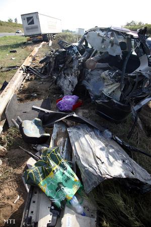 """Autóroncsok az M7-es autópályán, Balatonszárszó közelében, miután egy, az autópálya külső sávjában haladó terményszállító kamion nekiütközött a belső sávban közlekedő személygépkocsinak, és a járművet """"feltolta"""" a két pályatestet elválasztó szalagkorlátra 2012. augusztus 6-án."""